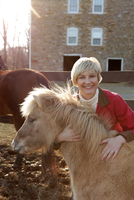 Portrait of mid adult woman standing with pony 11015301862| 写真素材・ストックフォト・画像・イラスト素材|アマナイメージズ