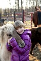 Portrait of young girl outdoors, hugging pony 11015301864| 写真素材・ストックフォト・画像・イラスト素材|アマナイメージズ