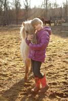 Portrait of young girl outdoors, hugging pony 11015301865| 写真素材・ストックフォト・画像・イラスト素材|アマナイメージズ
