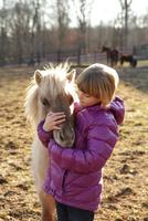 Young girl outdoors, hugging pony 11015301866| 写真素材・ストックフォト・画像・イラスト素材|アマナイメージズ