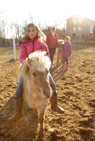 Young girl riding pony, mother and sister watching from behind 11015301875| 写真素材・ストックフォト・画像・イラスト素材|アマナイメージズ