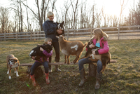 Mother and daughters outdoors, hugging goats and pet dog 11015301885| 写真素材・ストックフォト・画像・イラスト素材|アマナイメージズ
