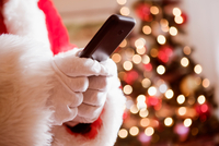 Cropped view of man in santa costume holding cell phone