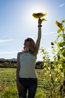 Young woman holding up sunflower head in field on organic farm