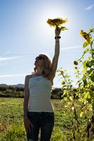 Young woman holding up sunflower head in field on organic farm 11015302012| 写真素材・ストックフォト・画像・イラスト素材|アマナイメージズ