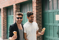 Young male couple eating ice cream cones in city