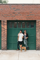 Young male couple with dog leaning on garage eating ice cream cones