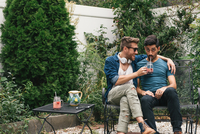 Young male couple sitting in garden drinking cocktails