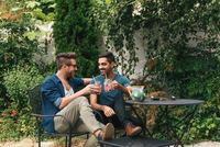 Young male couple sitting in garden raising a cocktail toast