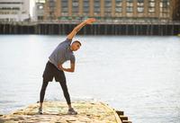 Man stretching on pier, Wapping, London, UK 11015302220| 写真素材・ストックフォト・画像・イラスト素材|アマナイメージズ