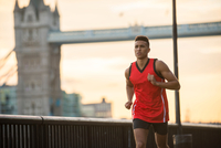 Man running by riverside, Tower Bridge in background, Wapping, London, UK 11015302239| 写真素材・ストックフォト・画像・イラスト素材|アマナイメージズ