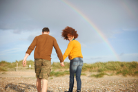 Couple walking on beach towards rainbow 11015302270| 写真素材・ストックフォト・画像・イラスト素材|アマナイメージズ