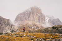 Hiker walking, Mount Lagazuoi in background, Dolomite Alps, South Tyrol, Italy