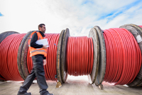 Worker walking past reels of electrical cable at cable storage facility 11015302323| 写真素材・ストックフォト・画像・イラスト素材|アマナイメージズ