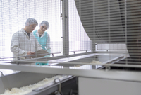 Workers in discussion in Asian food factory 11015302347| 写真素材・ストックフォト・画像・イラスト素材|アマナイメージズ