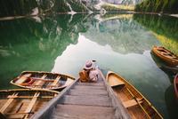 Woman relaxing on pier, Lago di Braies, Dolomite Alps, Val di Braies, South Tyrol, Italy 11015302430| 写真素材・ストックフォト・画像・イラスト素材|アマナイメージズ