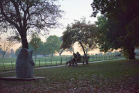 Silhouetted view of senior woman and daughter sitting on park bench in autumn park