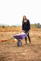 Portrait of mid adult woman pushing toddler daughter in wheelbarrow in pumpkin field