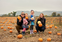 Portrait of parents and two daughters crouching in pumpkin field