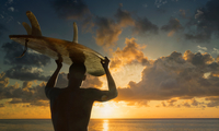 Silhouetted rear view of male surfer carrying surfboard on head watching sunset over sea, Rio De Janeiro, Brazil