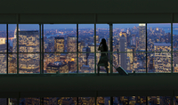 Silhouetted woman crossing city footbridge over New York cityscape at night, USA