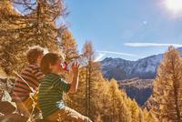 Two boys sitting on rocks, drinking from water bottles, Schnalstal, South Tyrol, Italy 11015303031| 写真素材・ストックフォト・画像・イラスト素材|アマナイメージズ
