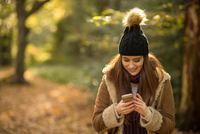 Young woman in forest, looking at smartphone, smiling