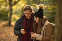 Young couple in forest, looking at smartphones