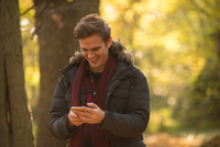 Young man in forest, looking at smartphone, smiling