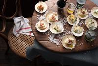Scallops in shells on table 11015303192| 写真素材・ストックフォト・画像・イラスト素材|アマナイメージズ