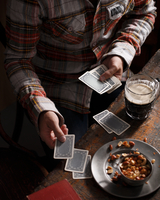 Cropped shot of man playing cards at pub table