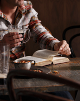 Cropped shot of man drinking beer and reading book at pub table