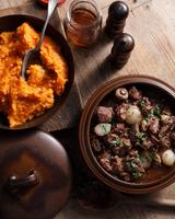 Bistro meal of beef burgundy in casserole dish on table 11015303217| 写真素材・ストックフォト・画像・イラスト素材|アマナイメージズ