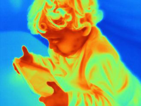 Thermal image of male toddler looking at digital tablet
