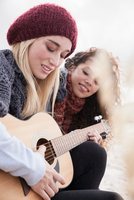 Two young women playing guitar at beach, Western Cape, South Africa