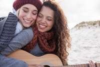 Portrait of two young female friends playing guitar at beach, Western Cape, South Africa