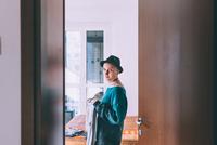 Doorway portrait of young woman wearing trilby standing in bedroom