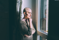 Portrait of young woman with shaved head gazing through window