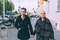 Young lesbian couple walking along city street holding hands