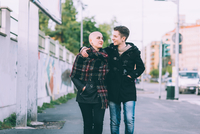 Young lesbian couple strolling along city street