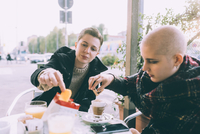 Two you female friends eating snack at sidewalk cafe