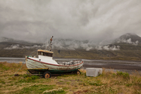 Old fishing boat at lakeside with moody sky, Seyoisfjorour, Iceland