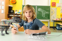 Portrait of boy with hand held computer and 3D model of tyrannosaurus rex