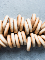 Overhead view of fresh bagels strung together 11015303409| 写真素材・ストックフォト・画像・イラスト素材|アマナイメージズ
