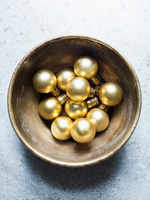 Overhead view of gold Christmas baubles in bowl 11015303412| 写真素材・ストックフォト・画像・イラスト素材|アマナイメージズ
