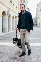 Mid adult man walking his dog in cobbled city street 11015303437| 写真素材・ストックフォト・画像・イラスト素材|アマナイメージズ