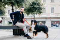 Man with dog smoking cigarette on city street bench 11015303443| 写真素材・ストックフォト・画像・イラスト素材|アマナイメージズ