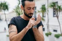 Mid adult man lighting cigarette 11015303453| 写真素材・ストックフォト・画像・イラスト素材|アマナイメージズ