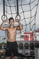 Portrait of young man training on exercise rings at rooftop gym in Bangkok