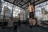 Young man training on exercise rings at rooftop gym in Bangkok